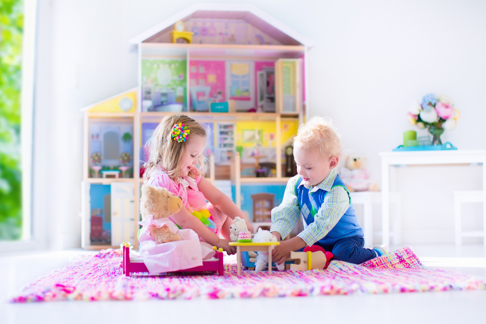 toddler dollhouse - Kids playing with doll house and stuffed animal toys. Children sit on a pink rug in a play room at home or kindergarten. Toddler kid and baby with plush toy and dolls. Birthday party for little child.