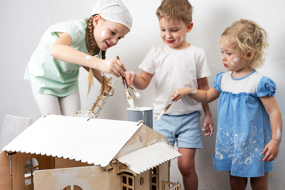 best dollhouses for boys - young kids painting a dollhouse