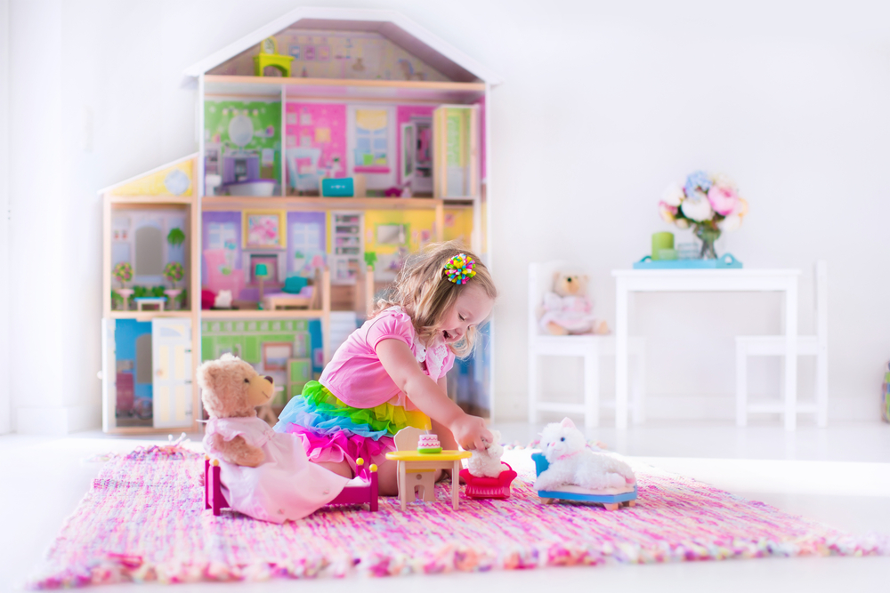 best barbie houses - barbie doll houses - photo Little girl playing toys siting on a pink rug in a play room at home