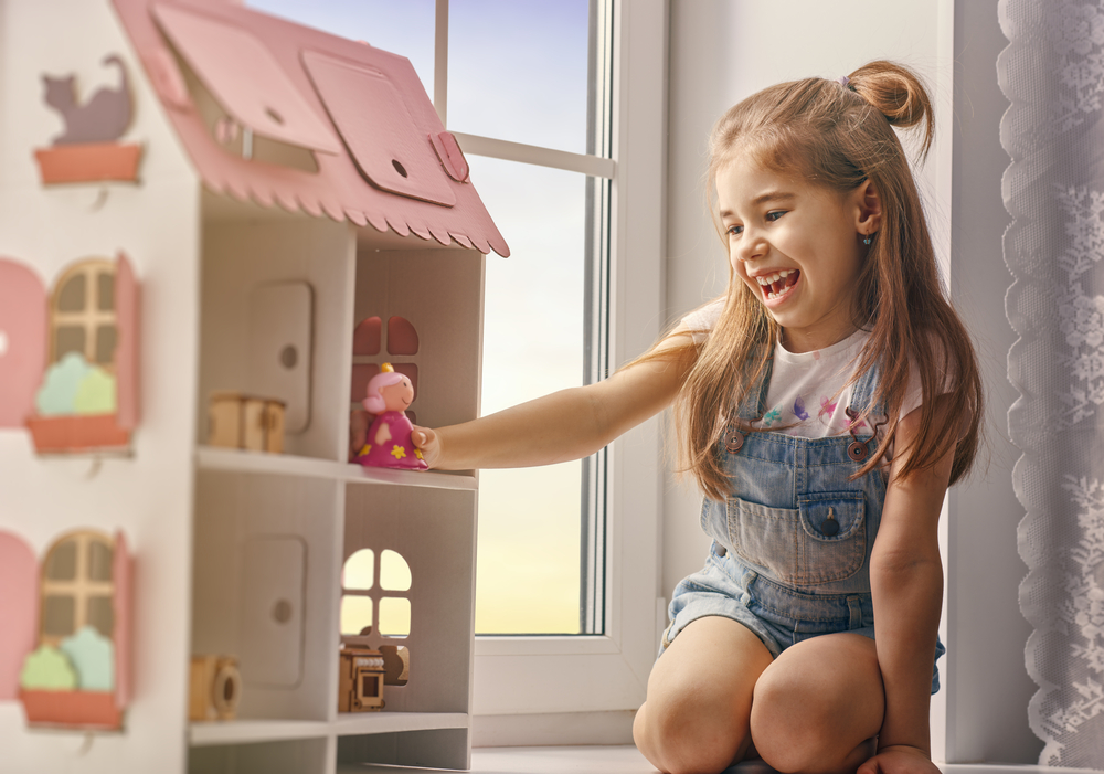dollhouses for kids - Happy girl plays with doll house and teddy bear at home. Funny lovely child is having fun in kids room.